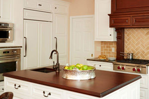 kitchen island featuring solid wood countertop on white cabinets