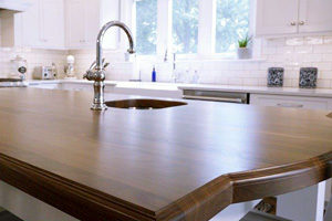kitchen island featuring solid wood countertop with under counter sink