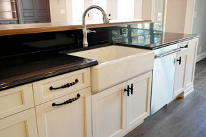 white kitchen cabinets with farmhouse style sink and granite countertops