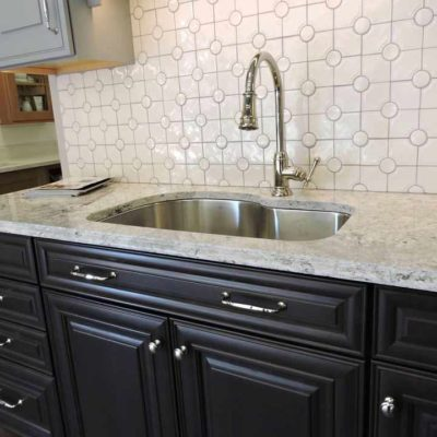 dark kitchen cabinets with stone countertop and deep stainless sink