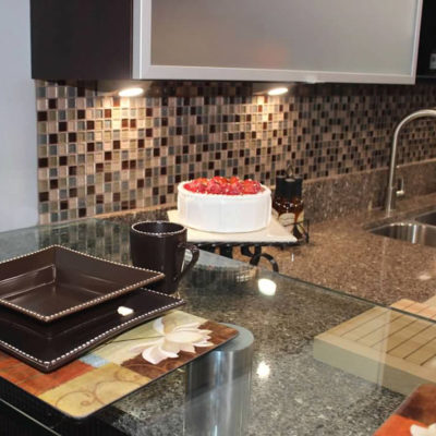 modern kitchen remodel with mosaic tile backsplash undercabinet lighting and granite countertops