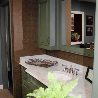 bathroom remodel display shows gray vanity and medicine cabinets with white vanity top and brushed nickel faucet