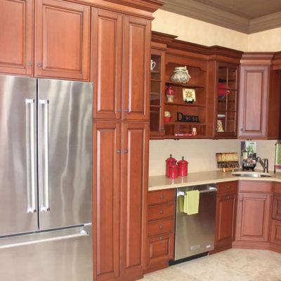 cherry kitchen cabinets with stainless steel appliances on display
